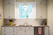 Patterned wallpaper, white cabinets, and penny-tile floors in a kitchen
