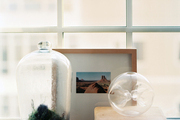 A terrarium and framed art on a windowsill