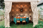A dining table set for an autumn meal in a tented canopy