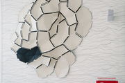 A mirrored piece of wall art hangs on textured wallpaper.