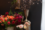 Ranunculus, roses, and flowering branches in ceramic and silver vessels in a floral studio.