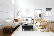 A white living room complimented with wooden furniture accents and a pastel color palette.