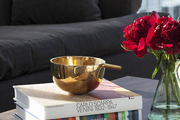 A gleaming copper bowl atop stacked art books in a Manhattan penthouse