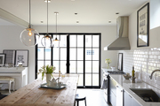 Three pendant lights from West Elm are suspended over a knotty-surfaced farm table in the kitchen.