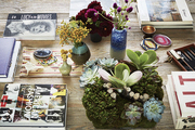 A mix of books, flowers in ceramic vases and a succulent arrangement on a coffee table