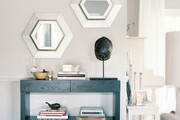 A trio of hexagonal mirrors above a wood console in an entryway