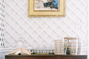 Lattice-covered walls in a dining room with a wooden table for displaying serving accessories