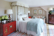 A plaid area rug beneath a bed with a ruffled canopy