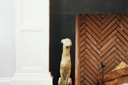 A dog statue beside a fireplace with a herringbone pattern