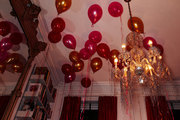 A large gold mirror and floating balloons reflect the glittering light from a tinsel covered chandelier