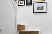 Curved stairs case below white wall covered in framed photos.