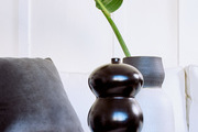 A detail of two ceramic vases on a white table.