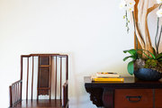 Tall, white orchids sit atop an Asian console table