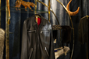 A detail of a leather jacket hanging in a store.