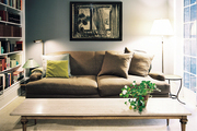 A stone-topped coffee table paired with a roll-arm couch and gray walls