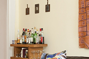 A handmade bar cart in the corner of an eclectic living room.