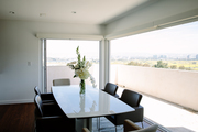 A glass dining room table with leather chairs and a nice view.