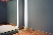 Gray walls, an upholstered stool, and a patterned rug in a dressing room