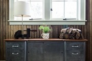 An industrial credenza in front of rustic wooden walls.