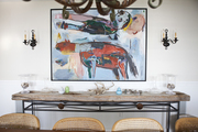 Large framed art between vintage light fixtures above natural wooden table.
