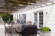 A covered patio is home to a weathered teak dining set