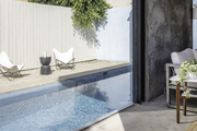 This is a pool house looking out to a pool in a fenced-in outdoor area.