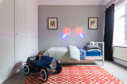 A contemporary kid's bedroom with a red rug and neon lights.