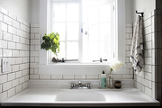 A wide basin farm-style sink underneath a recessed window.