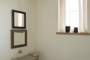 Natural wood beam and small vintage sing in white bathroom.