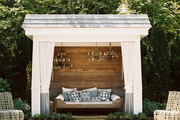 A pool house with vintage chandeliers hung above a daybed