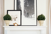A pair of boxwoods and framed black-and-white photographs on a white mantel