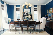 A blue dining room with a wooden table and a pair of white wingback chairs