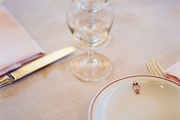 A place setting atop a linen tablecloth