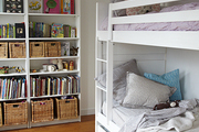 Toys and books on a shelf beside a bunk bed