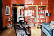 Red lacquered walls, herringbone hardwood floors, and a pair of gold shelving units in a living space