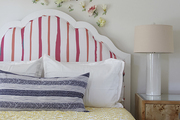 Floral wall treatment over striped headboard and bright bedding.
