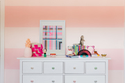 A white dresser in a kid's room with pink striped walls.