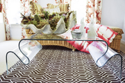 A curvy-legged lucite coffee table atop a geometric-patterned rug in the bedroom.