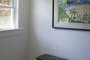 Large scale art hanging above vintage bench in white room.