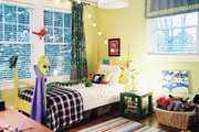 Yellow walls and a striped rug in a colorful child's room
