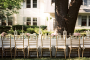 An outdoor dinner party with an elegant table and gold chairs