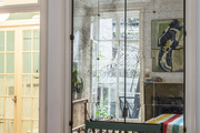 A green bench set against doors covered with antique mirror panes