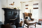 A leather wingback chair and a striped armchair flanking a black fireplace mantel