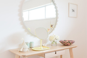 A whimsical vanity with an oversized round mirror.
