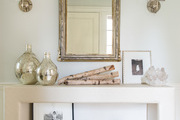 A detail of an entryway with a white console table with contemporary decor objects.