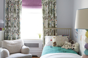 Colorful drapes hanging behind white and beige children's furniture.