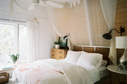 A neutral guest room with a canopy of white muslin
