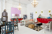 An antique birdcage, a classic chesterfield, a 1970s cocktail table, and a red console at Buckingham Interiors + Design