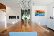 A long, wooden dining room table with a cityscape painting on the wall and a built in fireplace.