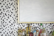 Spotted wallpaper and party essentials below gold framed art.